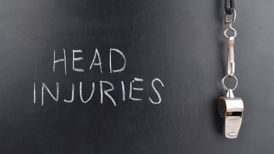 Chalkboard with the words Head Injury written in white chalk, with a coach whistle hanging from the blackboard