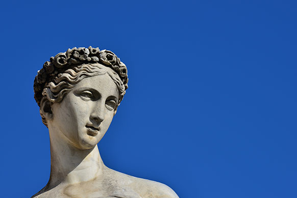 photo of a female Greek sculpture with blue sky background